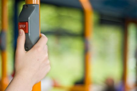 a childs thumb about to press the stop button on public transport.