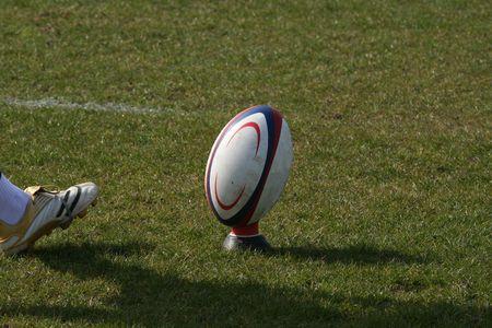 and rugby ball: jugador del rugbi que golpea la bola con el pie