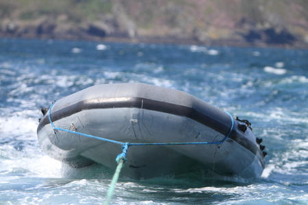 inflatable boat: Inflatable boat being towed Stock Photo