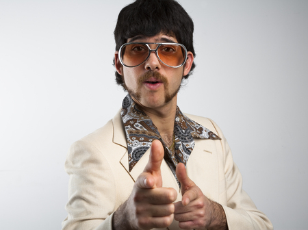 70s disco: Portrait of a retro man in a 1970s leisure suit and sunglasses pointing to the camera