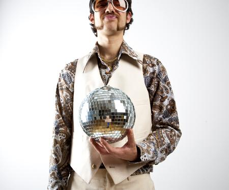 Portret van een retro man in een 1970 Leisure Suit en zonnebril met een discobal - spiegelbol