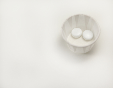 two white pills in a paper cup isolated on white