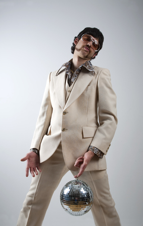 discoball: Low angle portrait of a retro man in a 1970s leisure suit and sunglasses holding a disco ball - mirror ball between his legs