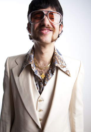 Portrait of a retro man in a 1970s leisure suit and sunglasses smiling to the camera
