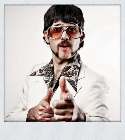 Filtered image of a Retro 1970s man in a leisure suit pointing to the camera - instant film style photo Foto de archivo