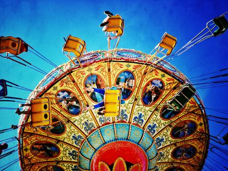 filtered image of an amusement park swing ride Foto de archivo