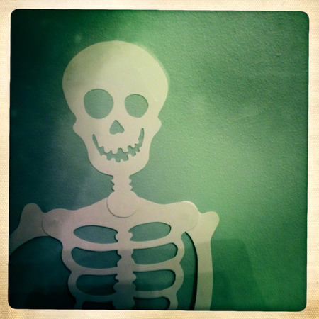 filtered image of a Halloween skeleton hanging on a wall
