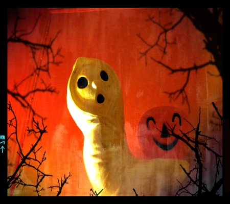 spectre: Vintage plastic ghost holding jack o lantern amongst branches - Halloween decoration