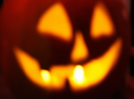 defocused Halloween jack o lantern with glowing candles background