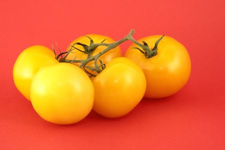 Yellow Tomato isolated on red background Stock Photo