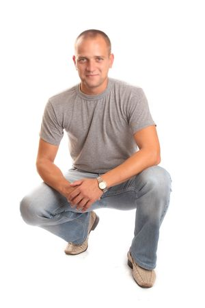 Portrait of a casual male in jeans crouching