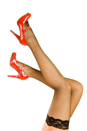 A pair of womens legs up in the air with red shoes and stockings.