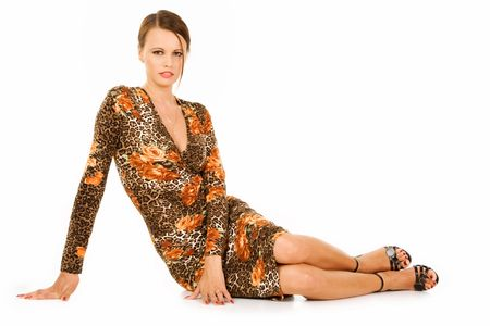 Fashionable teenager wearing patterned dress sat on ground isolated on white background.
