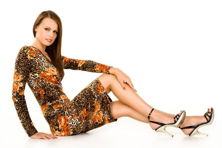 Fashionable teenager wearing leopard print dress sat on ground, isolated on white background.