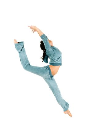 An isolated view of an teenage gymnast doing stretching exercises.