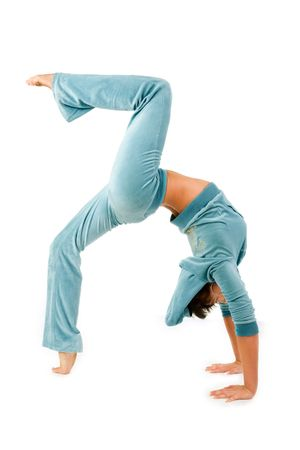 Young woman in a backward bend gymnastics pose, with one foot and both hands on the ground, and one leg in the air. Isolated against a white background.