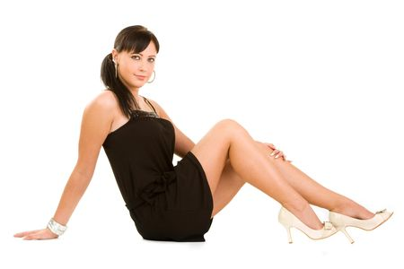 sitting on the ground: Smiling fashionable young woman wearing black dress, isolated on white background.