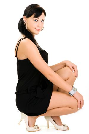 crouching: Smiling young woman wearing fashionable black dress crouching on ground, isolated on white background. Stock Photo
