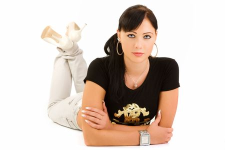 Pretty young woman wearing fashionable clothes lying on floor, isolated on white background.