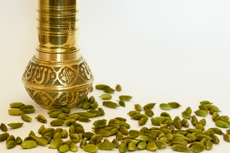 Green cardamom pods with spice grinder in the background Stock Photo