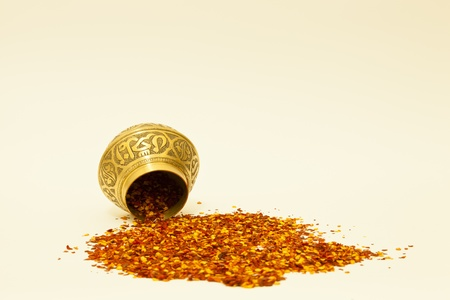 Engraved spice bowl with chilli flakes spilling from it