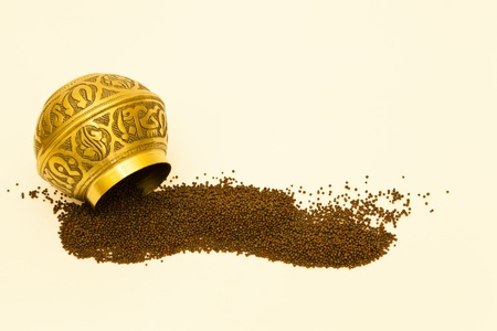 Brown mustard seeds tipped from an engraved spice bowl
