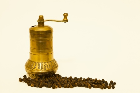 Black peppercorns and a traditional brass spice grinder on a plain surface