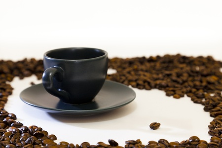Espresso coffee cup and saucer and one select coffee bean surrounded by a ring of beans