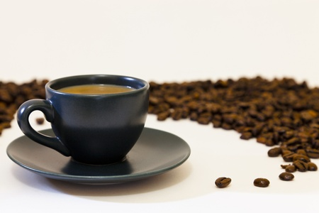 That special cup of coffee. Espresso coffee cup and saucer and a few select coffee beans surrounded by a ring of beans