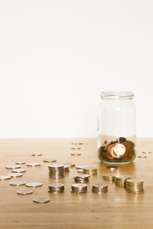 Coins in a glass jar, and also stacked and spread out on an old table while being counted.