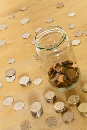 Coins in a glass jar, and also stacked and spread out on an old table while being counted.  Shot at a angle to imply money slipping away.