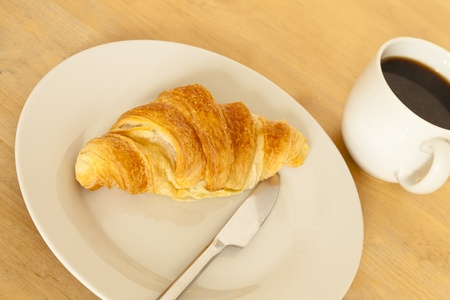 Croissant and coffee for breakfast photo