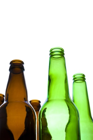 Looking up at empty green and brown beer bottles with a white background. photo