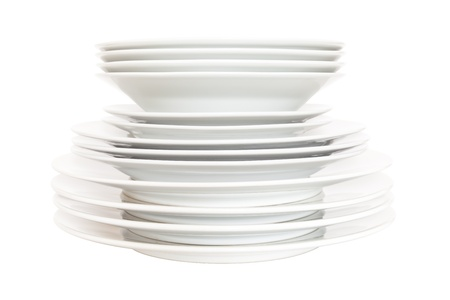Plates and bowls stacked up and isolated on a white background.