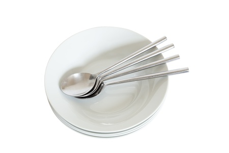 Four white bowls and four dessert spoons stacked and ready for use. Isolated on a white background.