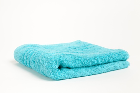 Folded fluffy blue towel isolated on a white background photo