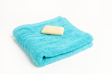 Folded fluffy blue towel with a bar of soap isolated on a white background