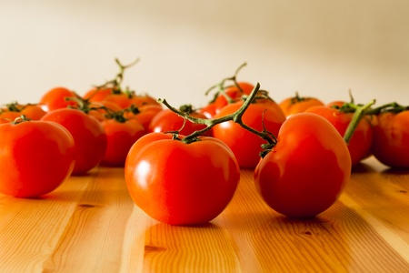 Fresh vine tomatoes spread out on a pine table