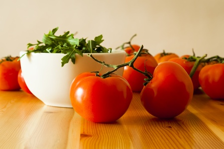 Fresh vine tomatoes and a bowl of rocket leaves spread out on a pine table