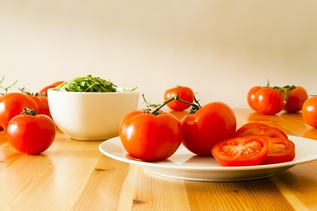 Fresh vine tomatoes spread out on a pine table around a plate with a sliced tomato and a bowl of rocket leaves. Stock Photo
