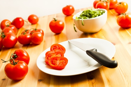 A sliced tomato and knife on a plate placed on a kitchen table. More fresh whole vine tomatoes and a bowl of rocket spread are also on the table.