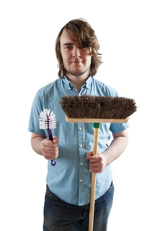Young man ready to clean up holding brush and broom.