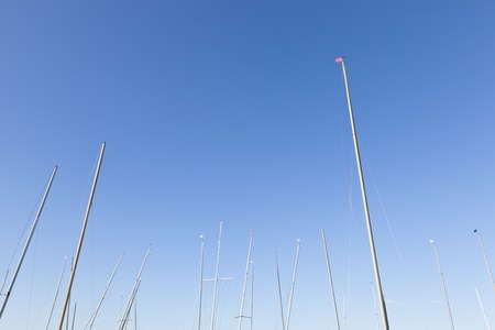 Many yacht masts standing high against a blue sky Stock Photo