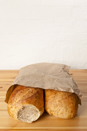 Two loaves of brown wholemeal bread wrapped in a brown paper bag
