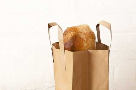 Brown wholemeal loaf in a brown paper carrier bag in a rustic kitchen environment Stock Photo