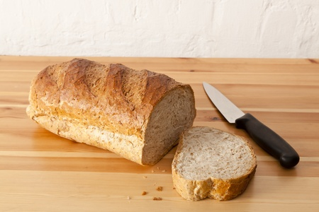 A brown wholemeal loaf with one thick slice cut off