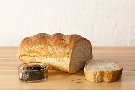 Wholemeal bread and blackcurrant jam in a rustic kitchen Stock Photo