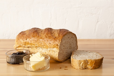 Wholemeal bread, butter and blackcurrant jam in a rustic kitchen environment Stock Photo