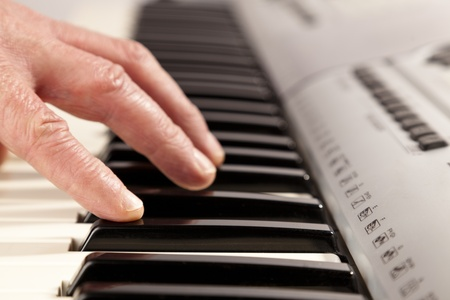 Older person playing an electric keyboard. Just the hand shown. Shallow depth of field. Stock Photo - 12871707