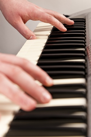 Young man playing an electric keyboard. Left and  right hand shown Stock Photo - 12871743